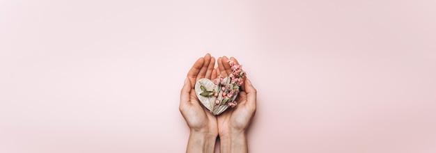 Płaskie Ukształtowanie Rąk Kobiety Trzymającej Drewniane Serce Na ścianie W Delikatnym Kolorze. Premium Zdjęcia