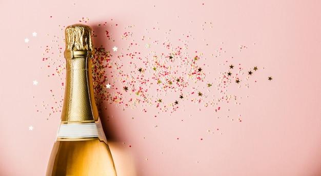 Płaskie ukształtowanie uroczystości. butelka szampana z posypką na różowym tle. Premium Zdjęcia