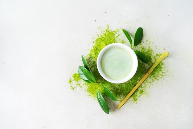 Płaskie ułożenie miski ekologicznej zielonej herbaty matcha w proszku z łyżką chashaku Premium Zdjęcia