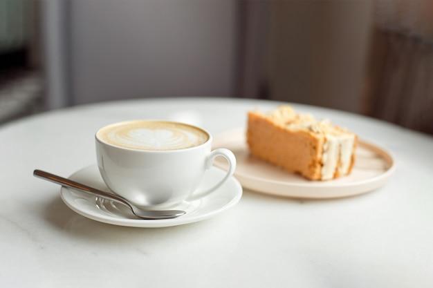 Plasterek Karmelowego Ciasta I Widelec Po Prawej Stronie. Filiżanka Gorącej Kawy Premium Zdjęcia