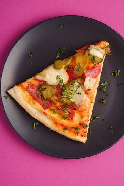 Plasterek Pizzy Z Pepperoni, Salami, Stopionym Serem Mozzarella, Piklami I Koperkiem W Czarnej Płycie Na Różowym Fioletowym Tle, Widok Z Góry Premium Zdjęcia
