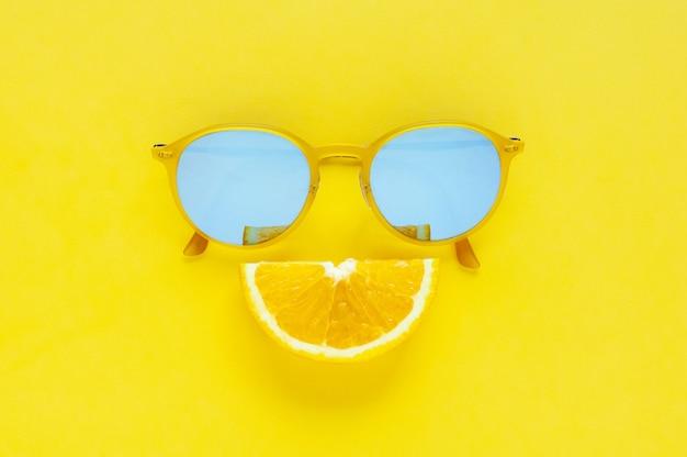 Plasterek pomarańczowa owoc ustawia jako uśmiechu usta i żółci okulary przeciwsłoneczni na żółtym tle. Premium Zdjęcia