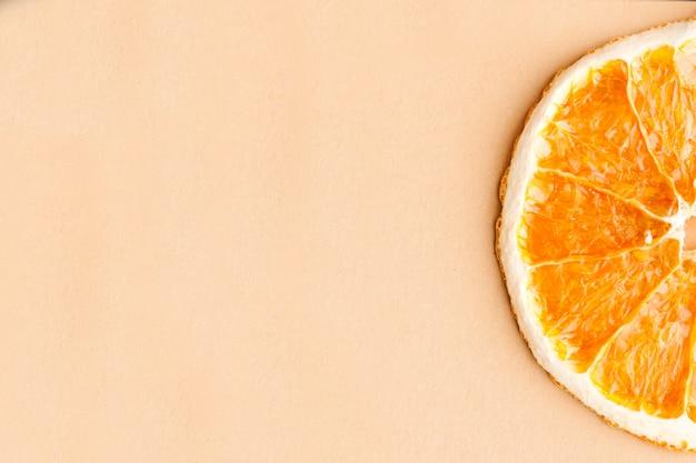 Plasterek Suszonej Pomarańczy Na Jasnobrązowym Tle Z Miejscem Na Tekst. Minimalizm, Koncepcja żywności. Premium Zdjęcia