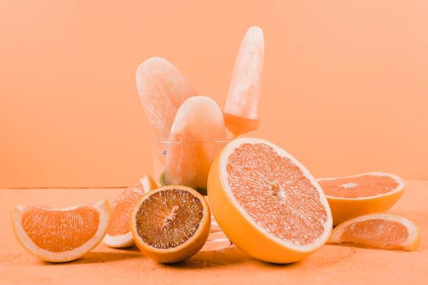 Plasterki grejpfrutów i pomarańczy z popsicles na pomarańczowym tle Darmowe Zdjęcia