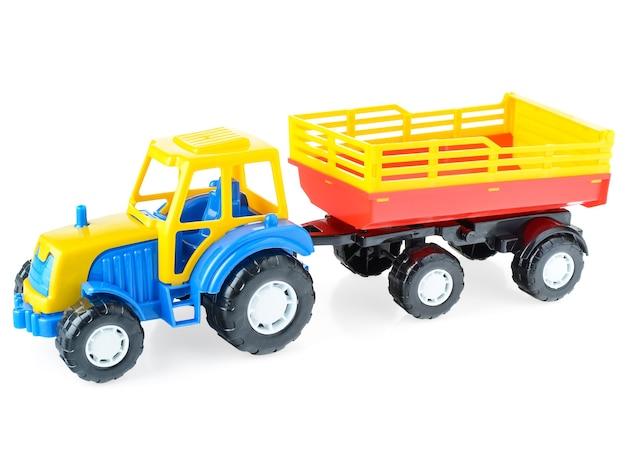 Plastikowa Ciężarówka Dla Dzieci Z Przyczepą Na Białym Tle, Zbliżenie. Jasny, Zabawkowy Samochodzik Dla Dzieci. Premium Zdjęcia
