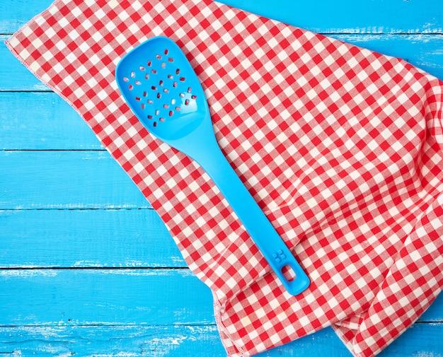 Plastikowa Niebieska łyżka Z Otworami Na Czerwonej Tekstylnej Serwetce Premium Zdjęcia