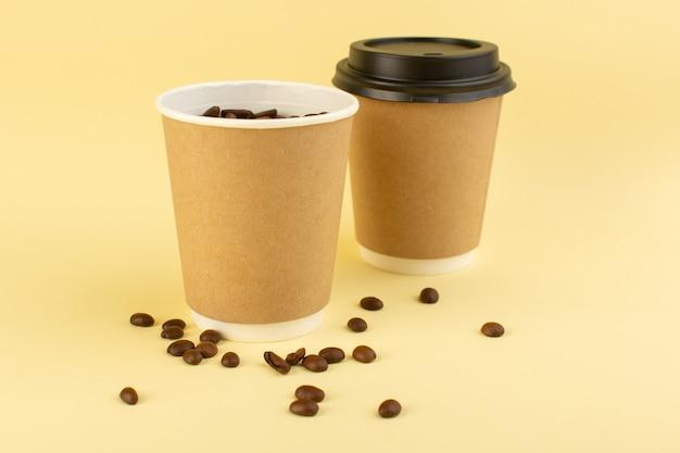 Plastikowe Kubki Do Kawy Z Brązowymi Ziarnami Kawy Na żółtej Powierzchni Darmowe Zdjęcia