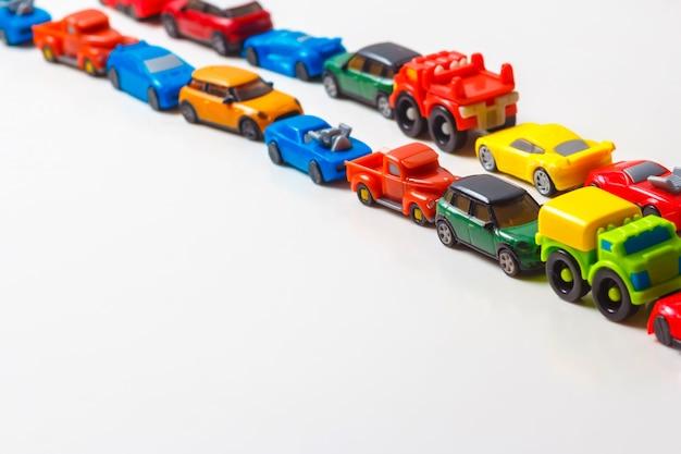 Plastikowe, Wielokolorowe Samochodziki Są Ustawione W Linii Na Białym Tle Premium Zdjęcia