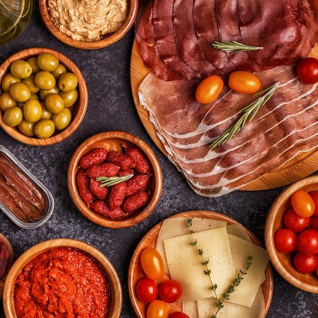 Plastry Jamon, Chorizo, Kiełbasa, Miski Z Oliwkami, Pomidory, Anchois, Puree Z Ciecierzycy, Ser. Premium Zdjęcia