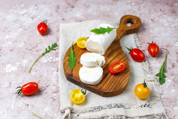 Plastry Koziego Sera Na Desce Z Rukolą, Pomidorami Koktajlowymi. Gotowy Do Jedzenia. Darmowe Zdjęcia