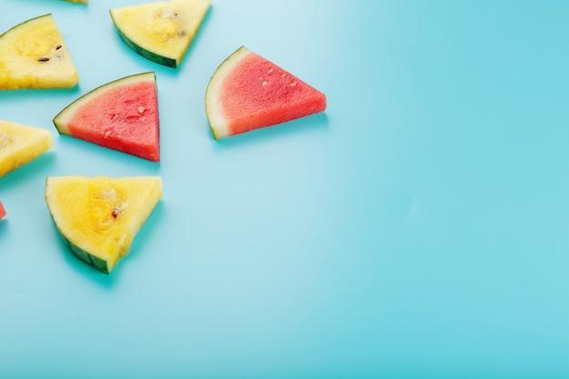 Plastry świeżych kawałków żółtego i czerwonego arbuza na niebiesko. Premium Zdjęcia