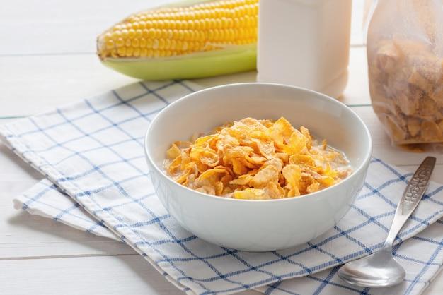 Płatki Kukurydziane W Misce Z Mlekiem I Płatki Zbożowe Płatki Kukurydziane W Plastikowym Opakowaniu Premium Zdjęcia