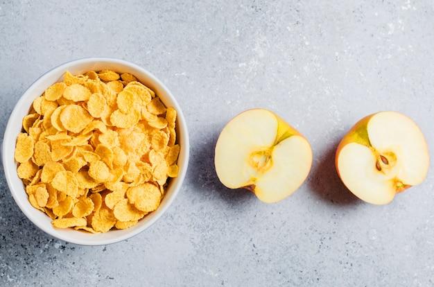 Płatki Kukurydziane W Niebieskim Plasterku Cup I Apple. Przydatne śniadanie Rano. Skopiuj Miejsce Premium Zdjęcia