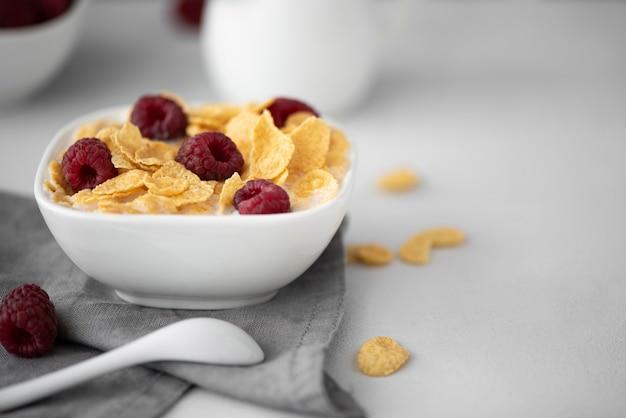 Płatki Kukurydziane Z Mlekiem I Malinami Na Białym Stole Premium Zdjęcia