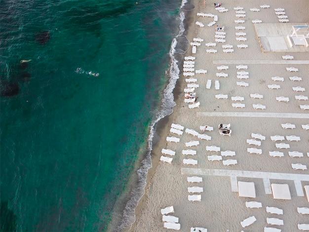 Plaża I Leżaki Nad Morzem Ze Szmaragdową Wodą. Letnie Wakacje Nad Morzem. Premium Zdjęcia