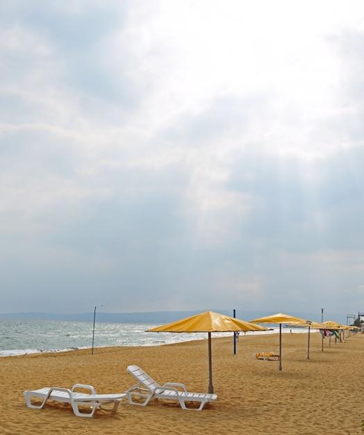 Plaża Piaszczysta Z Parasolami, Leżakami. Bez Ludzi Premium Zdjęcia