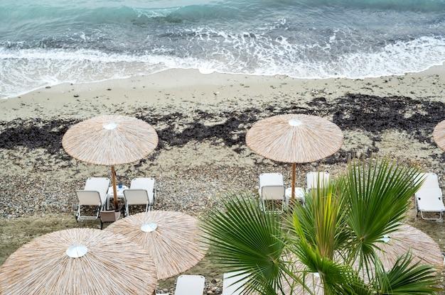 Plaża Z Leżakami, Parasolami Na Wybrzeżu Morza Egejskiego W Grecji Premium Zdjęcia