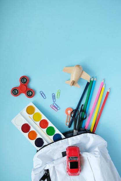 Plecak z różnymi kolorowymi artykułami na stole. Premium Zdjęcia