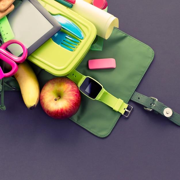 Plecak z szkolnymi dostawami na czarnym tle. Premium Zdjęcia