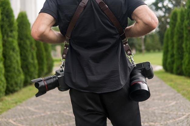 Plecy Profesjonalnego Fotografa W Czarnej Koszuli Z Dwoma Aparatami I Ramiączkami Na Tle Zielonego Ogrodu. Premium Zdjęcia