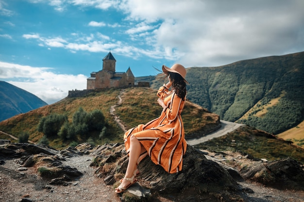Plenerowy Podróż Stylu życia Brunetki Kobiety Turysta Pozuje Na Górach I średniowiecznym Kościół Premium Zdjęcia