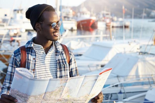 Plenerowy Portret Afrykańskiego Mężczyzny Wyglądającego Na Szczęśliwego Przed Podróżą, Czekającego Na Przyjaciół W Porcie, Trzymającego Papierową Mapę, Podekscytowanego I Radosnego, Przewidującego Przygody, Miejsca I Dobre Wrażenia Darmowe Zdjęcia