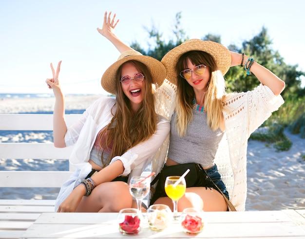 Plenerowy Portret Dwie Siostry Bijące Przyjaciółkę, Która Dobrze Się Bawi, ściska Uśmiechając Się I Robiąc Grymasy Na Barze Na Plaży, Ubrania W Stylu Boho Hipster, Pije Smaczne Koktajle, Letnie Wakacje Nad Oceanem. Darmowe Zdjęcia