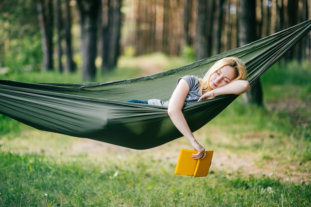 Plenerowy portret młody piękny blondynki dziewczyny dosypianie w hamaku w pogodnym lato lesie z ebook w jej ręce. Premium Zdjęcia