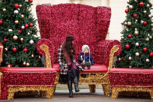 Plenerowy portret uśmiechnięta kobieta i mała dziewczynka w bożenarodzeniowych dekoracjach na ulicie miasto. szczęśliwa rodzina z małym dzieckiem. zimowe i świąteczne wakacje koncepcji. Premium Zdjęcia