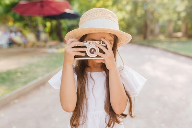 Plenerowy Portret Zainspirowanej Dziewczynki Spędzającej Czas W Parku I Fotografującej Widoki Przyrody. Dziecko W Kapeluszu Z Długimi Brązowymi Włosami Trzymając Aparat Stojący Na Drodze Darmowe Zdjęcia