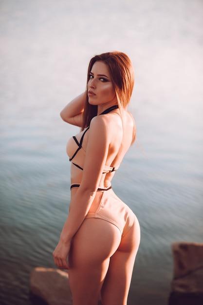 Plenerowy Strzał Piękny Młody Kobieta Model W Bikini Pozyci Na Plaży I Patrzeć Kamerę. Premium Zdjęcia