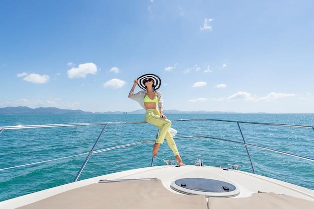 Plenerowy Strzał Urocza Młoda Kobieta W Lato Kostiumu I Kapeluszu Obsiadaniu Na Krawędzi Jachtu Premium Zdjęcia
