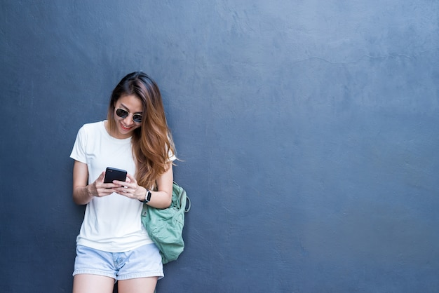 Plenerowy stylu życia portret ładna seksowna młoda azjatykcia dziewczyna w podróży i szkła projektujemy na szarości ścianie Darmowe Zdjęcia