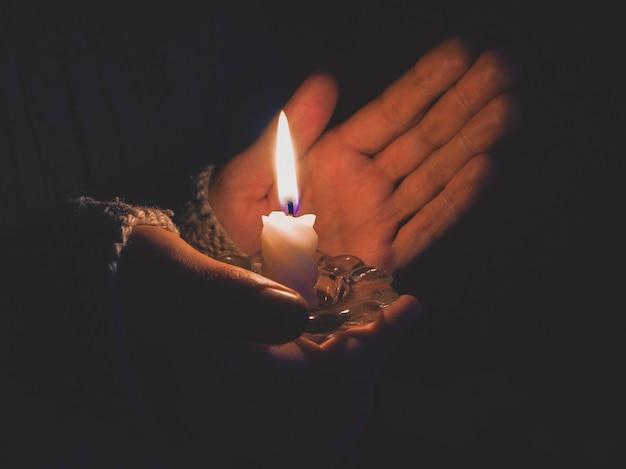 Płonącą świeczkę W Rękach Kobiet W Nocy. Premium Zdjęcia