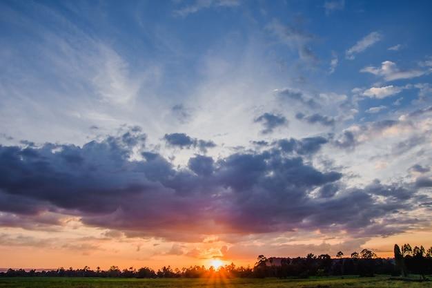 Płonące niebo i morze podczas zachodu słońca w żywych kolorach i imponujących formacjach chmur po deszczu i burzy. Premium Zdjęcia