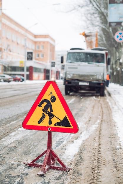 Pług odśnieżny usuwa śnieg z ulicy miasta. znak drogowy ostrzegawczy. praca pojazdu odśnieżającego odśnieżarki. czyszczenie zaśnieżonych zamarzniętych dróg. Premium Zdjęcia