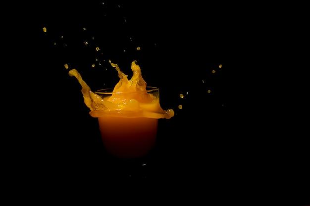 Pluśnięcie Sok Pomarańczowy Na Czarnym Tle Premium Zdjęcia