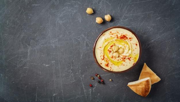 Płyta hummus z płaskim chlebem pita, ciecierzycą i przyprawami. widok z góry, miejsce na kopię. Premium Zdjęcia