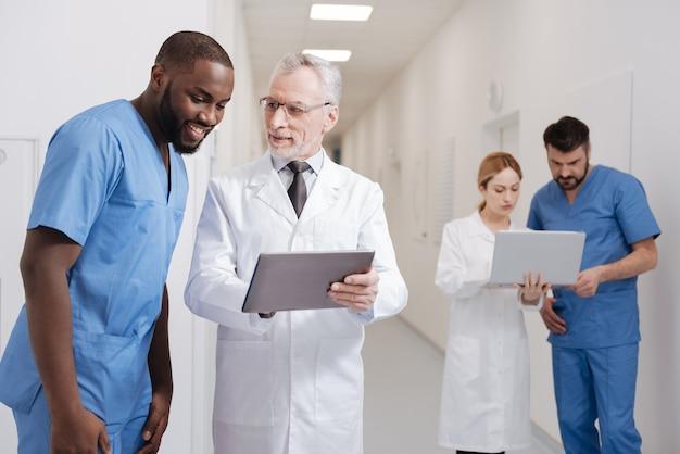 Po Prostu Zobacz Różnicę. Radosny, Wykwalifikowany Pediatra W Podeszłym Wieku, Cieszący Się Pracą W Szpitalu I Pracy Z Tabletem, Podczas Gdy Inni Koledzy Korzystają Z Laptopa W Tle Premium Zdjęcia