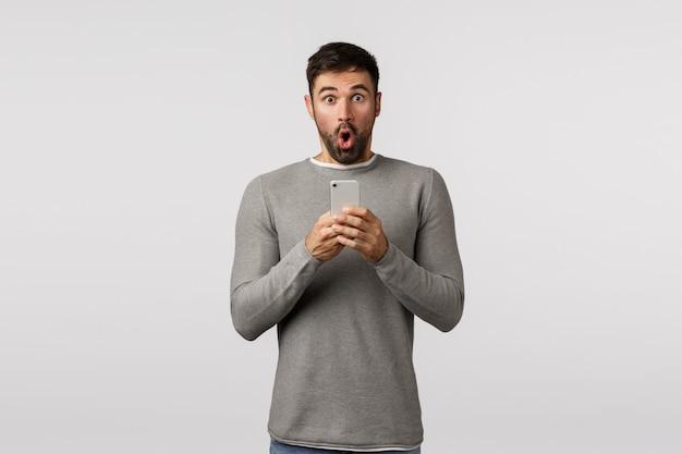 Pod Wrażeniem I Zafascynowany, Brodaty Kaukaski Mężczyzna W Szarym Swetrze Wyjmuje Swój Telefon, Aby Nagrać Niesamowite Wydarzenie, Składając Usta Z Trudem łapiąc Powietrze, Powiedz Wow Omg, Trzymaj Smartfon, Fotografując Niesamowite Rzeczy Premium Zdjęcia