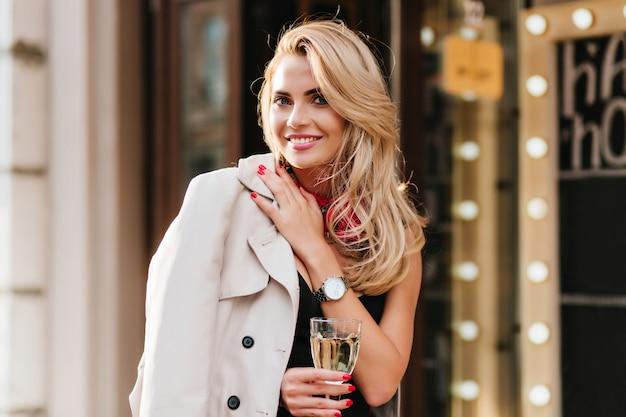 Podekscytowana Blondynka W Modnym Srebrnym Zegarku Na Rękę Pozuje Z Przyjemnością W Swoje Urodziny, Trzymając Kieliszek Do Wina. Urocza Dziewczyna Z Opaloną Skórą Pije Szampana I Bawi Się W Weekend. Darmowe Zdjęcia