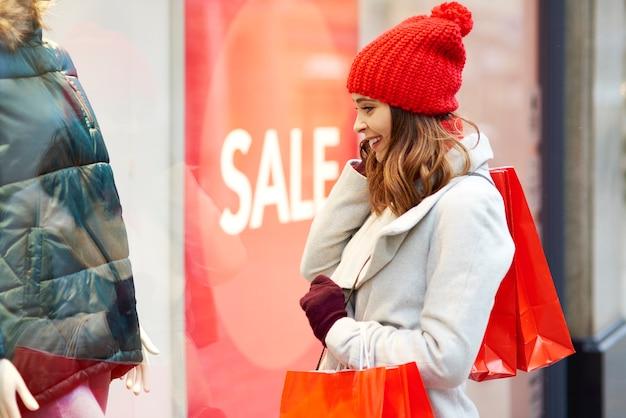 Podekscytowana Dziewczyna Patrząc Na Okno Sklepu Podczas Zimowych Zakupów Darmowe Zdjęcia