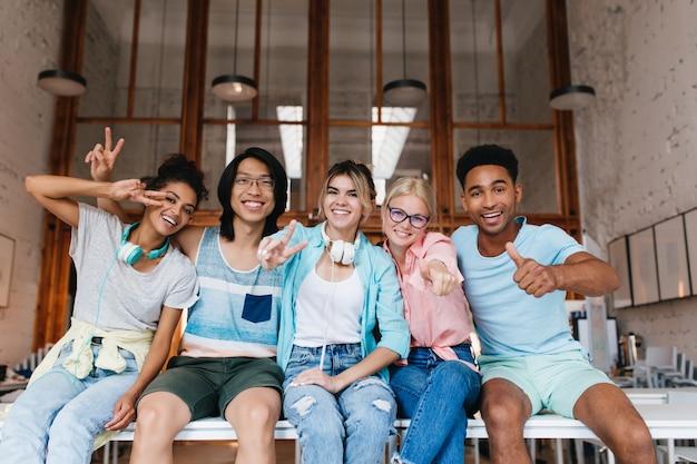 Podekscytowana Dziewczyna W Niebieskiej Koszuli Pokazuje Znak Pokoju, Ciesząc Się Towarzystwem Przyjaciela W Dobry Dzień. Wewnętrzny Portret Zadowolonych Studentów Z Zagranicy, Wygłupiających Się Do Zdjęć I śmiejących Się. Darmowe Zdjęcia
