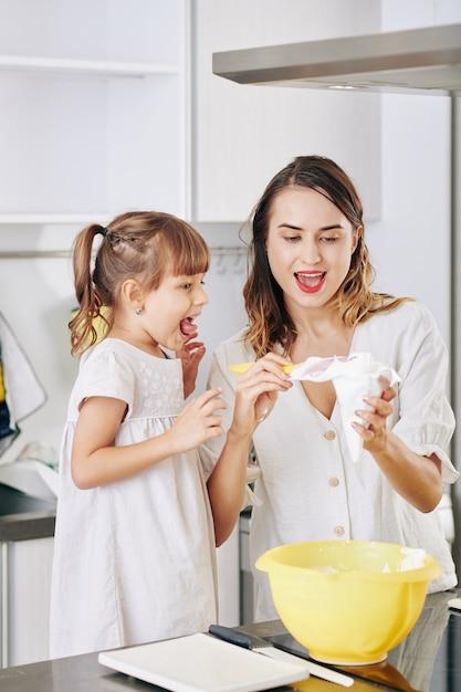 Podekscytowana Dziewczynka Patrzy Na Swoją Matkę, Przygotowując Tort Urodzinowy W Domu, Wypełniając Torbę Z Bitą śmietaną Premium Zdjęcia