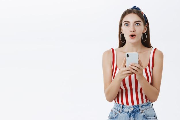 Podekscytowana I Pod Wrażeniem Atrakcyjna Stylowa Kobieta W Pasiastym Topie Trzymająca Smartfona Składane Usta W Zdumieniu Patrząc Zdziwiony I Zaintrygowany Gest Darmowe Zdjęcia