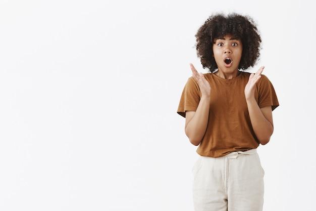 Podekscytowana I Podekscytowana, Oniemiała, Afroamerykańska Młoda Dziewczyna Z Kręconymi Fryzurami, Gestykulująca Z Dłońmi W Pobliżu Klatki Piersiowej, Otwierająca Usta I Opowiadająca Z Pasją, Co Się Stało, Dysząc, Będąc Zdumionym Darmowe Zdjęcia