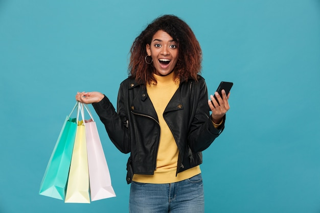 Podekscytowana Kobieta Afrykańska Gospodarstwa Torby Na Zakupy I Telefon Komórkowy. Darmowe Zdjęcia