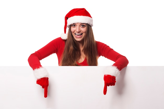 Podekscytowana Kobieta W Kapeluszu Santa Pokazując Na Pustej Tablicy Darmowe Zdjęcia