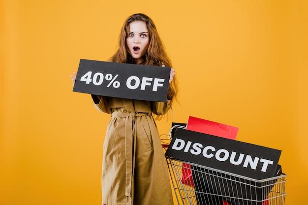 Podekscytowana kobieta w płaszczu ze znakiem 40% zniżki i kolorowe torby na zakupy w koszyku na białym tle nad żółtym Premium Zdjęcia