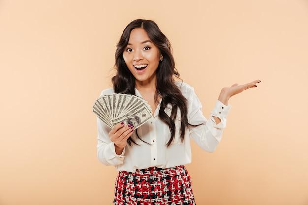 Podekscytowana Młoda Dama O Długich Ciemnych Włosach Gospodarstwa Fanem 100 Banknotów Dolarowych, Wyrażając Radość, Mając Dużo Pieniędzy Na Tle Brzoskwini Darmowe Zdjęcia